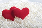 Red hearts on pearls background — Stock Photo