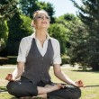 Beautiful woman meditating in the park — Stock Photo