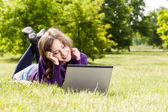 Young woman using laptop in the park — Stock Photo