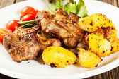 Grilled steaks and baked potatoes — Stock Photo