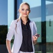 Young businesswoman using mobile phone on street — Stock Photo #46159457