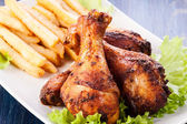 Chicken drumsticks with chips — Stock Photo