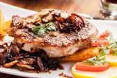 Fried pork chop with mushrooms and chips — Stock Photo