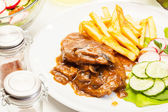 Pork chop with sauce, mushrooms and chips — Stockfoto
