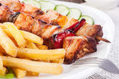 Grilled shashlik with chips — Stock Photo