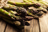 Bunch of young asparagus on wooden table — Stock Photo