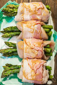 Asparagus wrapped in chicken and bacon in a baking dish — Stock Photo