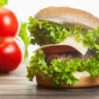 Cheeseburger with lettuce, onions and tomato in a sesame bun — Stock Photo #49490655