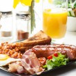 Full English breakfast with bacon, sausage, egg, baked beans and orange juice — Stock Photo #49495031