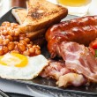 Full English breakfast with bacon, sausage, egg, baked beans and orange juice — Stock Photo #49495041