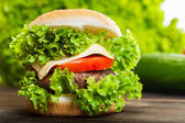 Cheeseburger with lettuce, onions and tomato in a sesame bun — Stock Photo