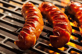Grilling sausages on barbecue grill — Photo