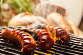 Grilling sausages on barbecue grill — Stok fotoğraf