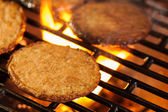 Hamburger patties on a grill with fire under — Stock Photo