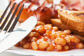Full English breakfast with bacon, sausage, fried egg and baked  — Stockfoto