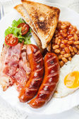Full English breakfast with bacon, sausage, fried egg and baked beans — Стоковое фото