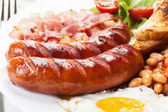 Full English breakfast with bacon, sausage, fried egg and baked beans — Stockfoto