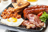 Full English breakfast with bacon, sausage, egg, baked beans and orange juice — Stock Photo