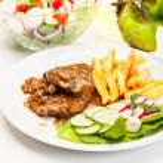 Pork chop met saus, paddestoelen en chips — Stockfoto #50738339