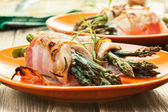 Baked asparagus wrapped in chicken and bacon — Stock Photo