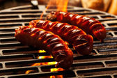Grilling sausages on barbecue grill — ストック写真