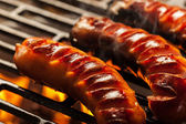 Grilling sausages on barbecue grill — Foto de Stock