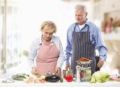 äldre par matlagning i köket — Stockfoto