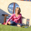 Foto Stock: Teenage student sitting on the grass outside the school