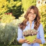 Beautiful mature woman gardening — Stock Photo