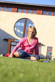 Teenage student sitting on the grass outside the school — Stock Photo