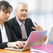 Businessman and Woman working on a Laptop — Stock Photo