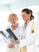 Female doctor talking with senior patient — Stock Photo