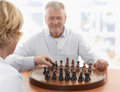 Couple playing chess in living room — Stock Photo