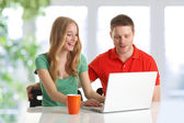 Happy couple browsing on computer — Stock Photo