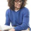 Young student learning on laptop at home — Stock Photo