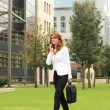 Businesswoman using mobile phone while walking on street — Stok fotoğraf