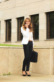 Businesswoman using mobile phone while walking on street — Stock Photo