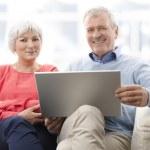 Пожилые супружеские пары с ноутбуком — Стоковое фото