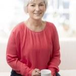 Smiling senior woman with tea — Stock Photo
