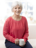 Smiling senior woman with tea — Stock Photo