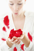 Beautiful, young woman blowing red rose petals from her palms — Stock Photo