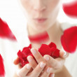 Woman blowing red rose petals — Stock Photo