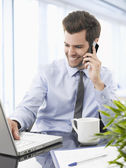 Smiling businessman talking on a mobile phone. — Stock Photo
