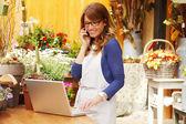 成熟した女性の花屋スモール ビジネス花店主の笑みを浮かべてください。 — ストック写真