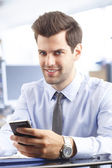 Young businessman reading a text message — Stok fotoğraf