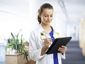 Beautiful female doctor examining the patient chart — Stockfoto