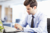 Young businessman working on laptop — Stock Photo