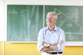 Smiling teacher standing in classroom — Stock Photo