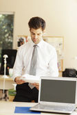 Young businessman reading in office — Stock Photo