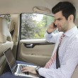 Stock Photo: Businessmworking in his car
